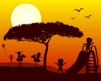 Jonge geitjes die Silhouetten spelen bij Zonsondergang Stock Foto