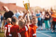 Jonge geitjes die Sportenconcurrentie winnen Het Team van het kinderenvoetbal met Trofee Jongens die Voetbalkampioenschap in Lage royalty-vrije stock foto