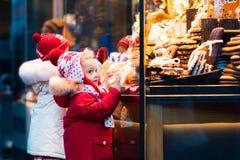 Jonge geitjes die suikergoed en gebakje op Kerstmismarkt bekijken royalty-vrije stock afbeelding