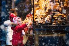 Jonge geitjes die suikergoed en gebakje op Kerstmismarkt bekijken stock foto