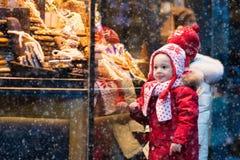 Jonge geitjes die suikergoed en gebakje op Kerstmismarkt bekijken stock afbeeldingen