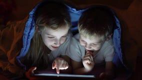 Jonge geitjes die tablet in bed spelen stock video