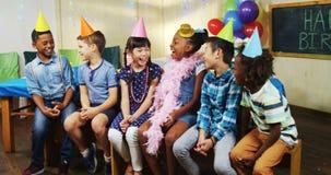 Jonge geitjes die terwijl het zitten samen tijdens verjaardagspartij 4k glimlachen stock video