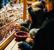 Jonge geitjes die traditioneel Kerstmisspeelgoed kopen bij de wintermarkt in Alsac Stock Foto's