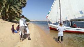 Jonge geitjes die traditionele ambachten op de banken van de Nijl verkopen stock videobeelden