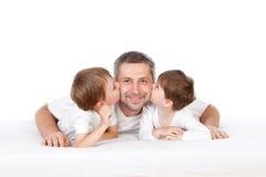 Jonge geitjes die vader kussen Royalty-vrije Stock Afbeeldingen