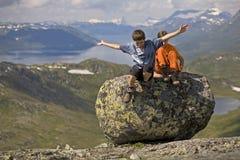 Jonge geitjes die van grote steen springen Royalty-vrije Stock Foto