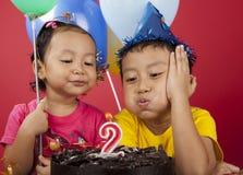 Jonge geitjes die verjaardagskaars blazen Stock Afbeelding