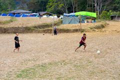 Jonge geitjes die voetbal in ricefield spelen Royalty-vrije Stock Foto's