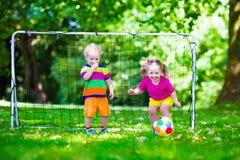 Jonge geitjes die voetbal in schoolwerf spelen Stock Foto
