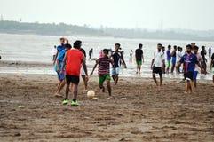 Jonge Jonge geitjes die Voetbal spelen bij Strand Stock Foto