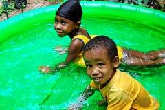 Jonge geitjes die weg in Pool koelen royalty-vrije stock fotografie