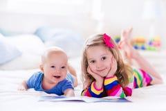 Jonge geitjes die in witte slaapkamer lezen royalty-vrije stock foto's