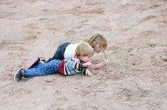Jonge geitjes die in zand spelen stock afbeeldingen