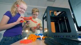Jonge geitjes in een schoollaboratorium, die met 3D gedrukte modellen werken stock video