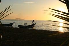 Jonge geitjes en boot in zonsondergang Stock Foto