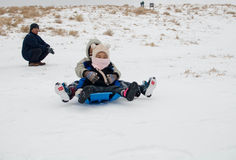 Jonge geitjes en ouderspel op de sneeuw Stock Foto