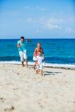 Jonge geitjes en vader het spelen op het strand royalty-vrije stock afbeelding