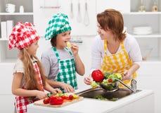 Jonge geitjes en vrouw in de keuken Royalty-vrije Stock Foto's