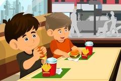 Jonge geitjes hamburger eten en gebraden gerechten die Stock Afbeelding