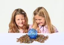Jonge geitjes - meisjes met het hoogtepunt van het besparingsvarken van geld stock afbeeldingen