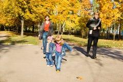 Jonge geitjes met ouders in de herfstpark Stock Afbeeldingen