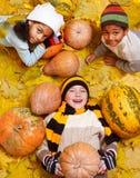Jonge geitjes onder gele bladeren en oranje pumpkings royalty-vrije stock afbeeldingen