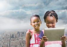 jonge geitjes op een tablet met stadsachtergrond Stock Foto's