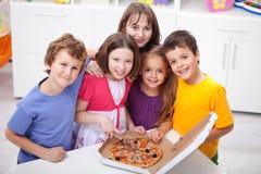 Jonge geitjes thuis met pizza Stock Fotografie