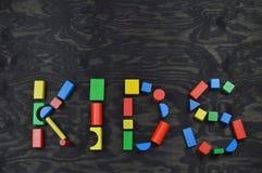 JONGE GEITJES uit kleurrijke houten stuk speelgoed blokken op zwarte royalty-vrije stock foto