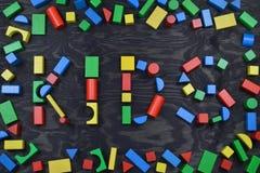 JONGE GEITJES uit kleurrijke houten stuk speelgoed blokken op zwarte Royalty-vrije Stock Afbeeldingen