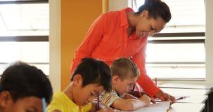 Jonge geitjes van de leraars de bijwonende school met hun klaswerk in klaslokaal stock videobeelden