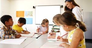 Jonge geitjes van de leraars de bijwonende school met hun klaswerk in klaslokaal stock footage