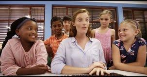Jonge geitjes van de leraars de bijwonende school op personal computer in klaslokaal stock video