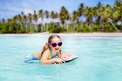 Jonge geitjesbranding op tropisch strand Vakantie met kind stock foto