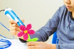 Jonge geitjeshanden die bloem met 3d drukpen maken Stock Afbeeldingen