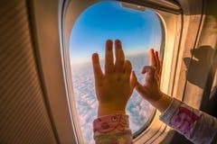Jonge geitjeshanden op het vliegtuigvenster royalty-vrije stock foto