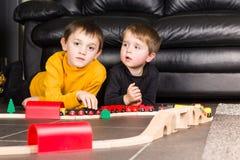 Jonge geitjesjongens die met houten treinen spelen royalty-vrije stock afbeeldingen