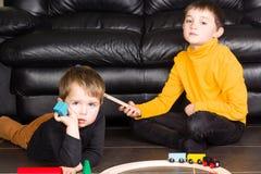 Jonge geitjesjongens die met houten treinen spelen stock afbeelding