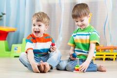 Jonge geitjesjongens met speelgoed in speelkamer stock foto