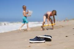 Jonge geitjespantoffels die op het strand liggen Stock Foto