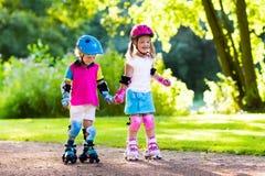 Jonge geitjesrol die in de zomerpark schaatsen stock fotografie