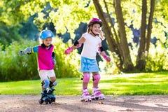Jonge geitjesrol die in de zomerpark schaatsen stock afbeeldingen