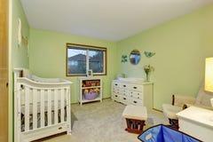 Jonge geitjesslaapkamer met wit meubilair en groene geschilderde muren Stock Fotografie