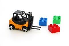 Jonge geitjesspeelgoed De gele vorkheftruckstuk speelgoed schepen kleuren kubussen stock foto