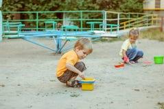 jonge geitjesspel in de zanddoos Stock Fotografie