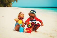 Jonge geitjesspel met zand op de zomerstrand Royalty-vrije Stock Fotografie