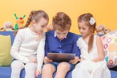 Jonge geitjesspel op tabletcomputer Stock Foto's