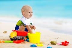 Jonge geitjesspel op tropisch strand Zand en waterstuk speelgoed royalty-vrije stock foto