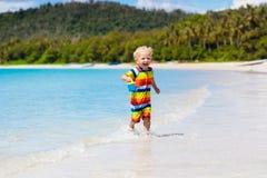Jonge geitjesspel op tropisch strand Zand en waterstuk speelgoed royalty-vrije stock afbeeldingen